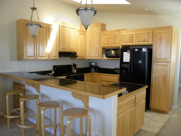 South unit kitchen with side by side refrigerator, icemaker, gas stove, microwave and all kitchen wares.