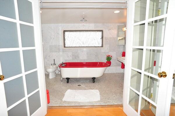 Clawfoot red bathtub in the main bathroom.  Rain shower faucet head on ceiling.