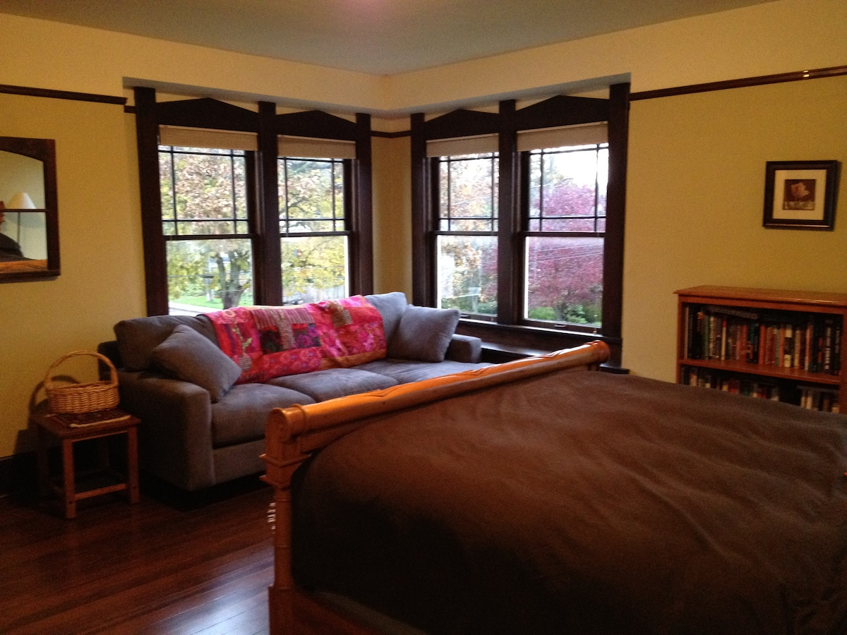 Master Bedroom. Queen bed, and corner window with couch.