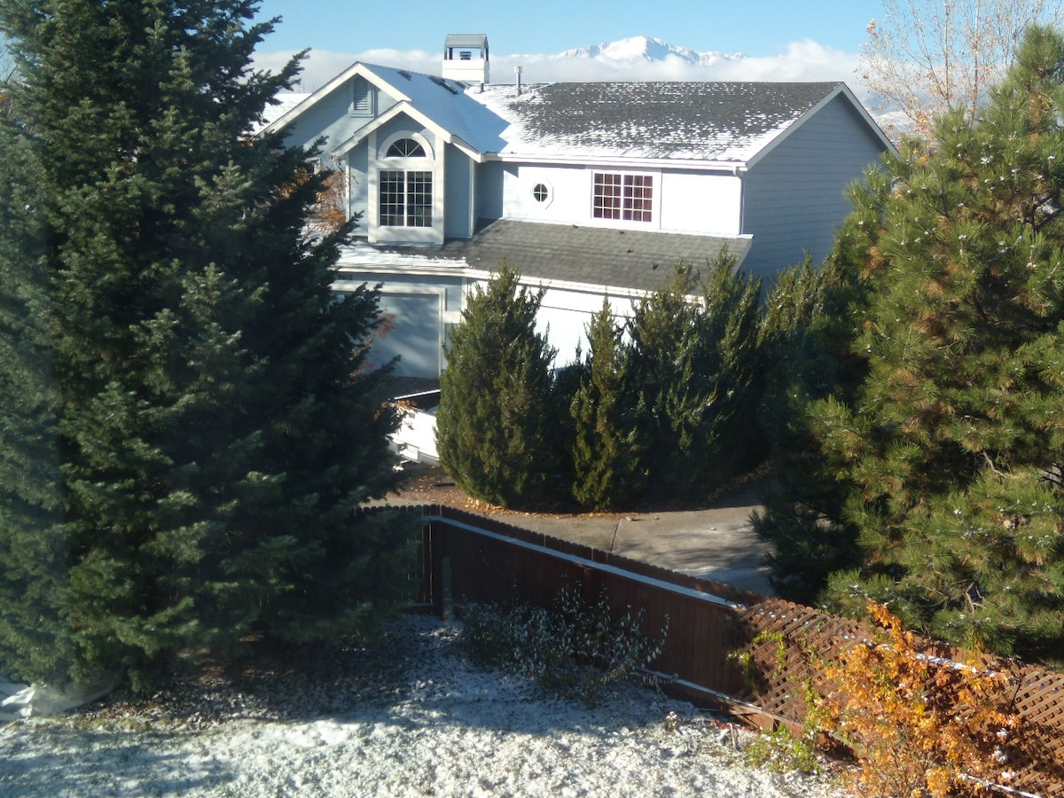 View of pikes peak (over the top of the next house) and evergreens from guest bedroom window