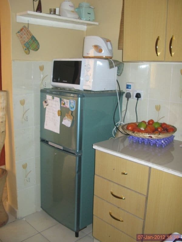 Kitchen with fridge, microwave, toaster, utensils, cooker