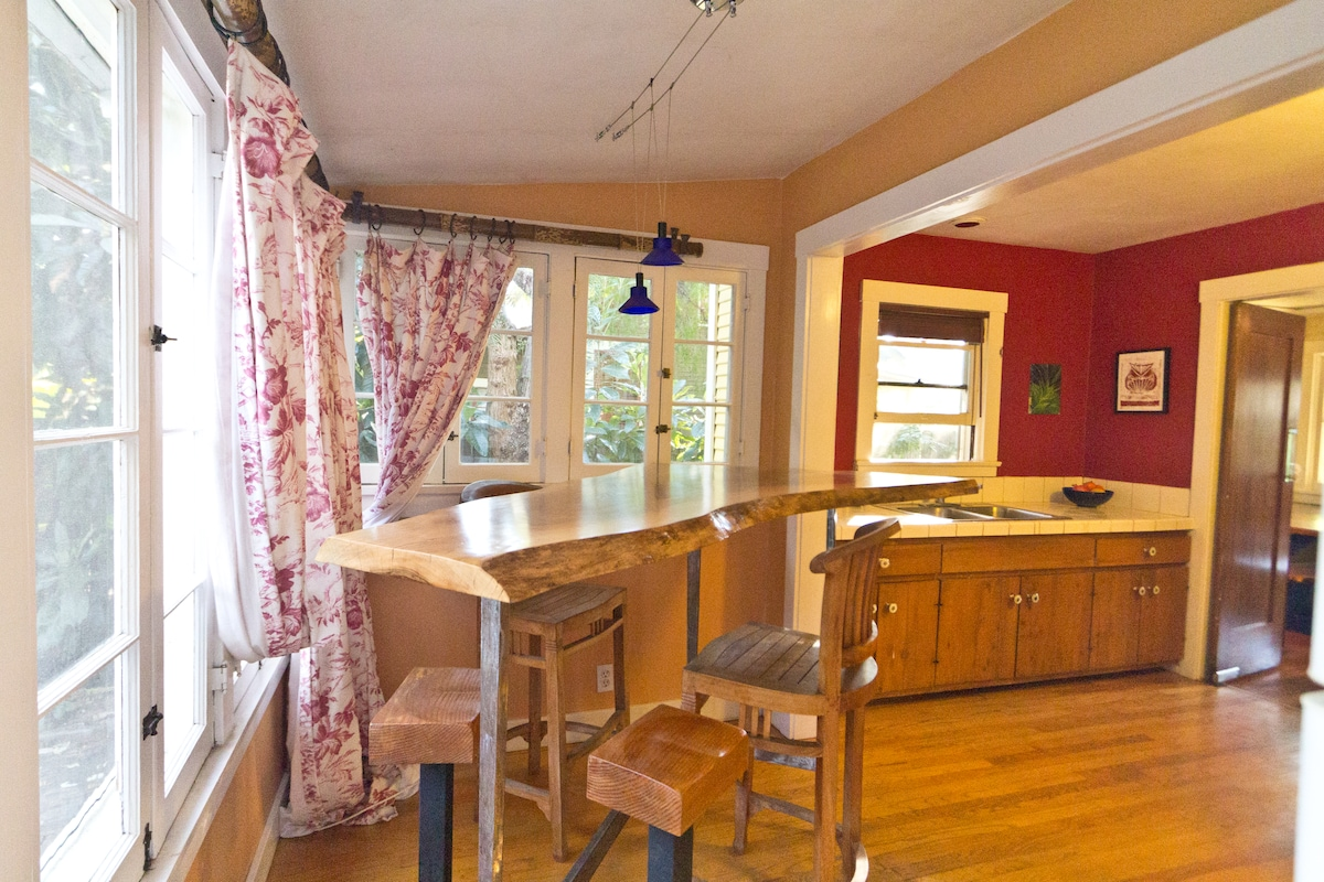 The cozy breakfast nook/bar is furnished with a custom three-legged wood slab table.