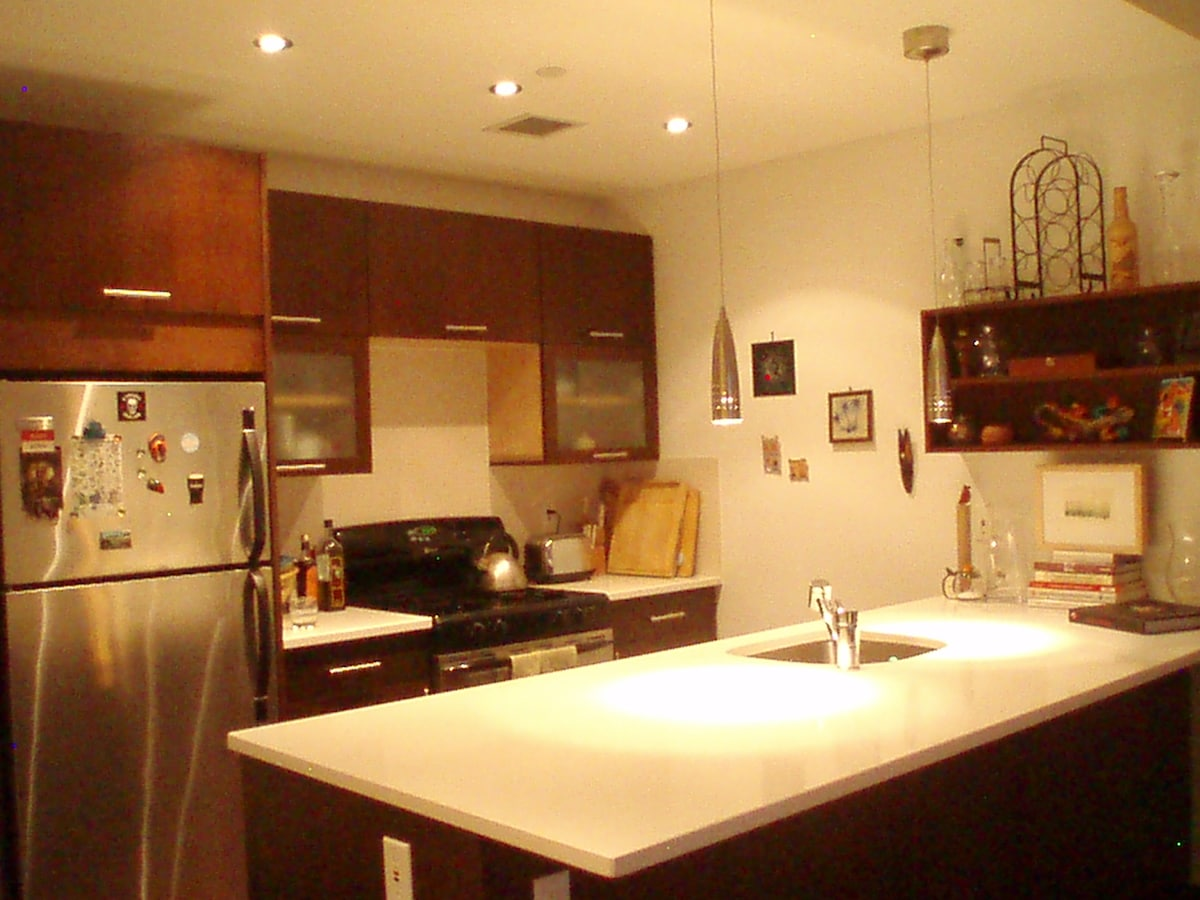 Open kitchen into livingroom with recessed lighting.