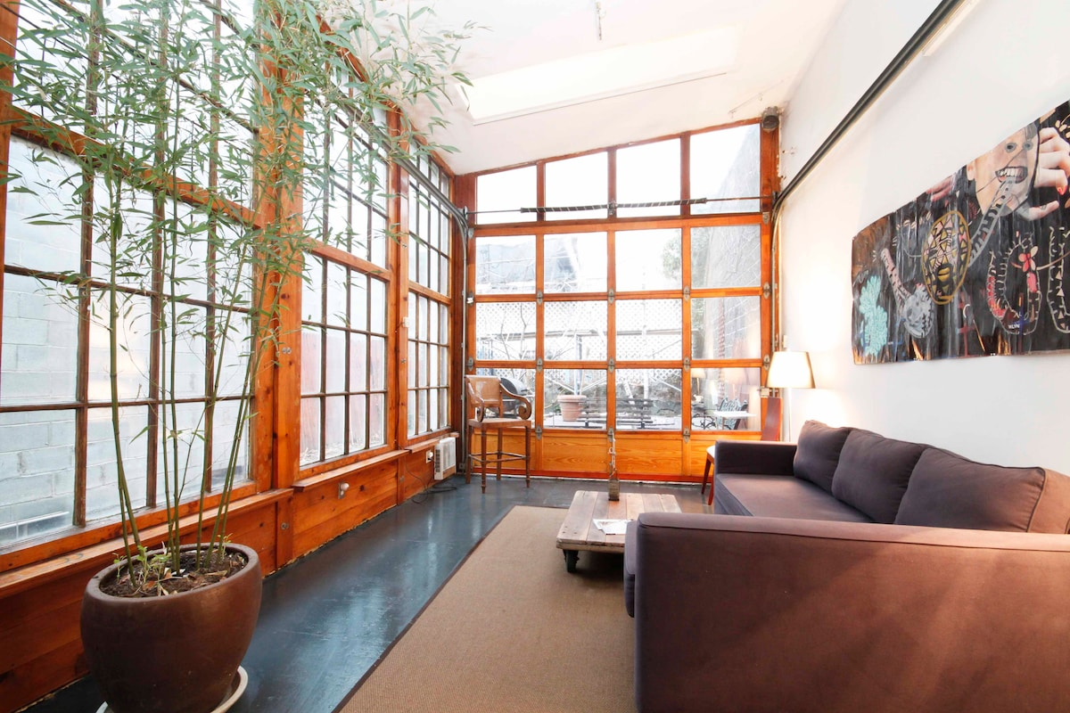 The back: Spectacular converted heated carriage house. Living room/ second bedroom. Glass garage door in the back lifts to include the garden in warm months. This room is splendidly heated.