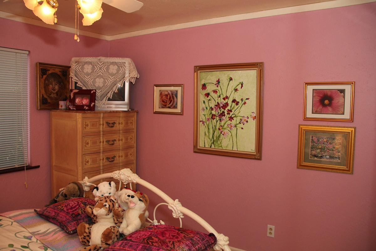 Other end of bedroom with art work.