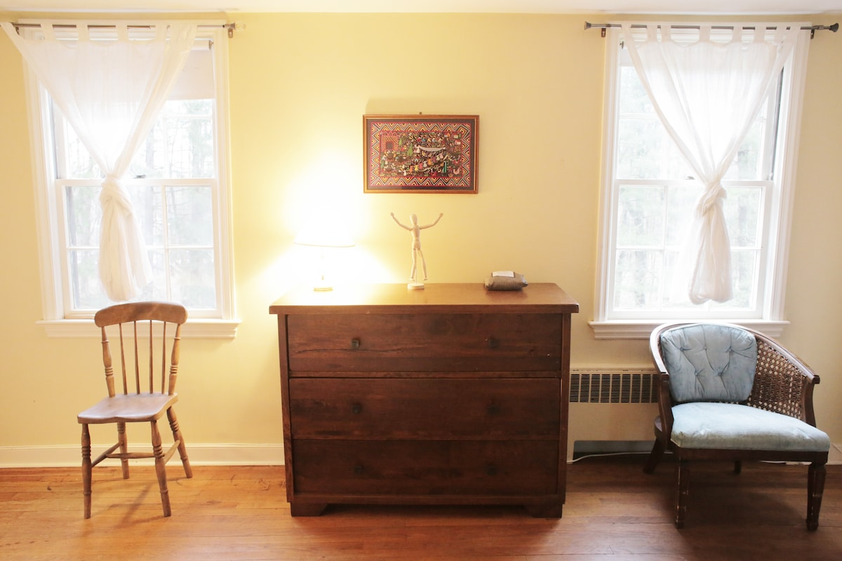 This quiet bedroom on one side of a Jack and Jill bathroom has a queen size bed and dresser.