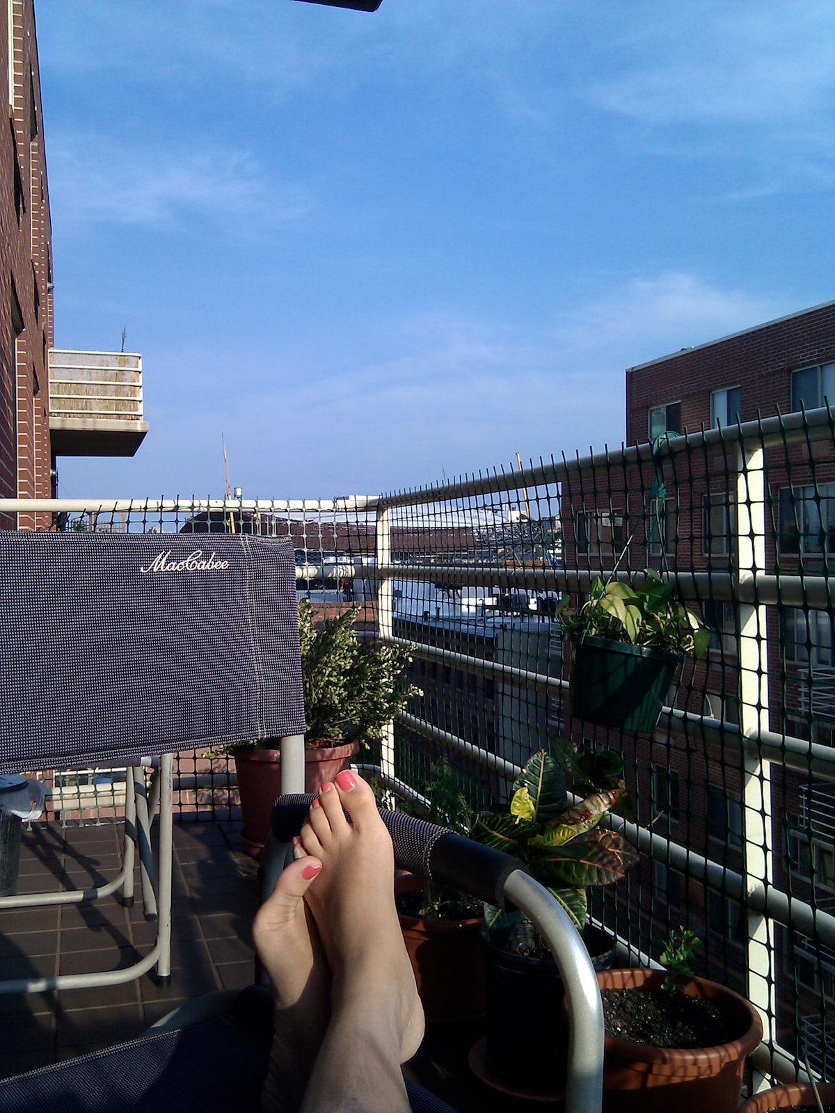 Just chilling, getting some sun, with my feet up on our balcony. Barclays Center is right ahead there. Life. Is. Good.
