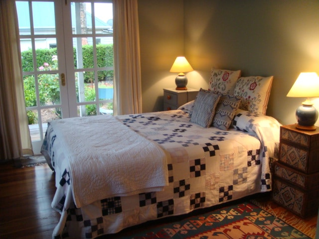 Queen bedroom with doors to porch. Ensuite to right.