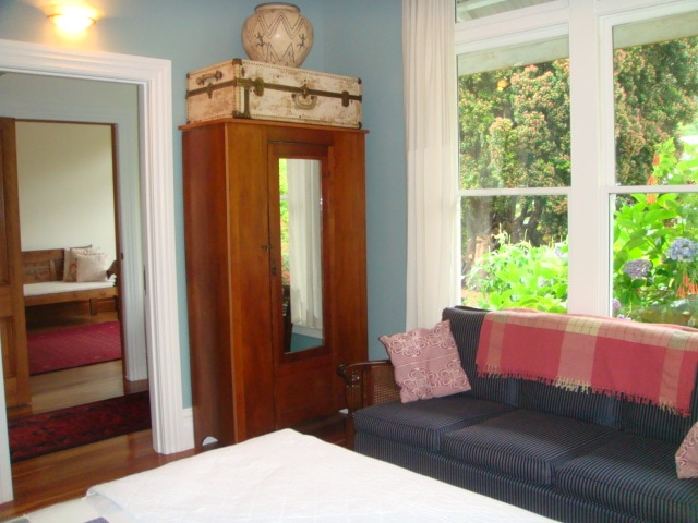 Blue room with view to front garden and shared lounge through hallway.