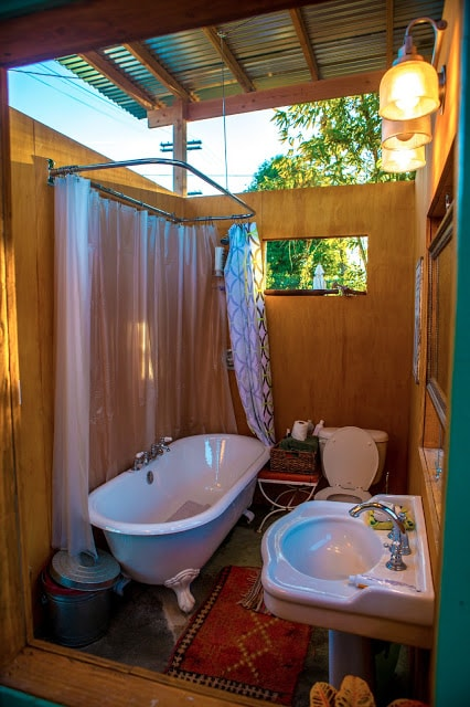 Luxe outdoor bathroom with claw-foot tub/shower, raised ceilings, sliding wooden panel windows.