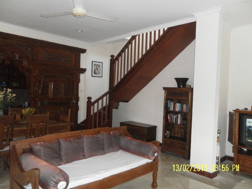 Stairs leading to the bedroom in the background. Kitchen entrance left. Living area ceiling fan top left