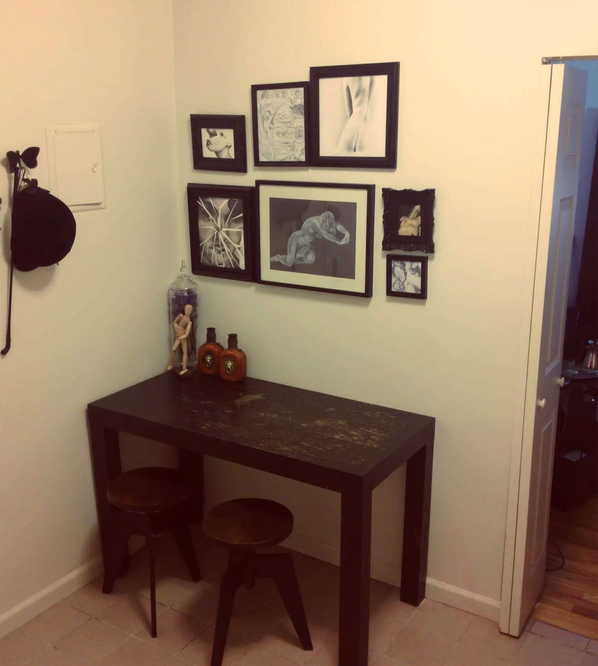 Dining table in kitchen.  Wall adorned w original art pieces.