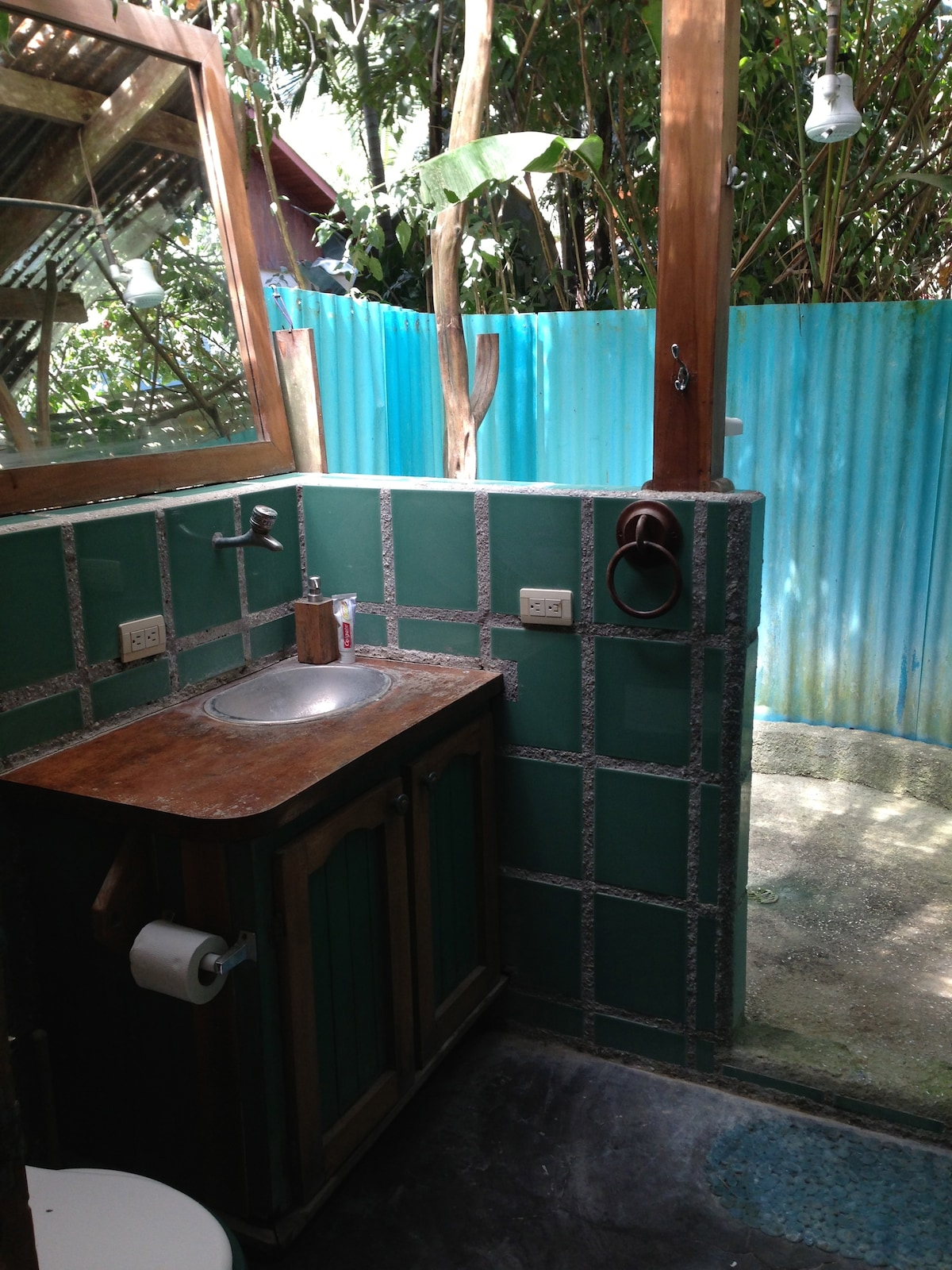 Indoor/outdoor bathroom surrounded by tropical plants