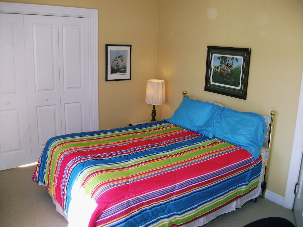 Guest room with queen bed, closet, desk, wifi, and AC.