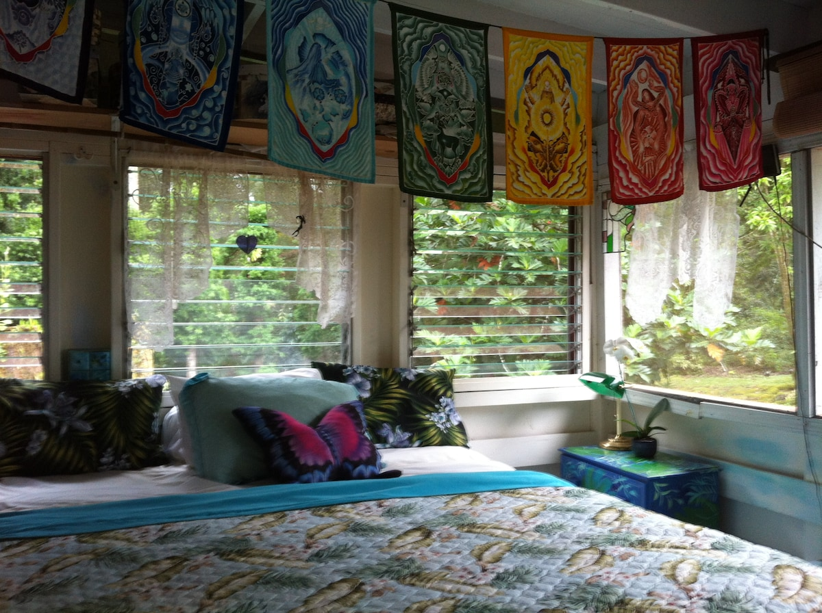 This upstairs guest room is surrounded by screens and windows for a full view of the garden.