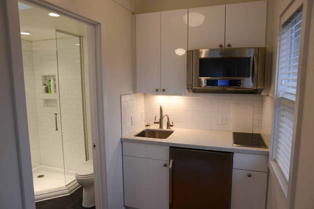 View of kitchenette next to bathroom with shower stall.