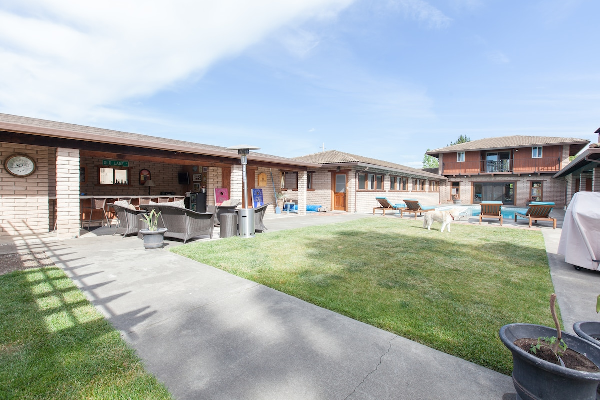 behind the pool is a beautiful lawn, outdoor bar, outdoor dining table and more..