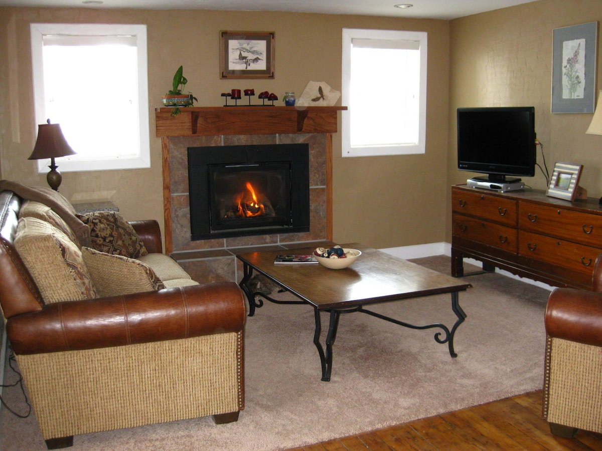 Living room showing cozy fireplace, flatscreen TV and comfy couch