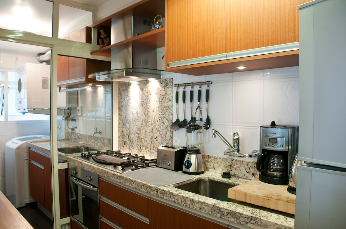 Modern and stylish kitchen with 5-burner cooktop, including electric grill.  Stove is both gas and electric.  Toaster, liquifier, coffee-maker, and water boiler.