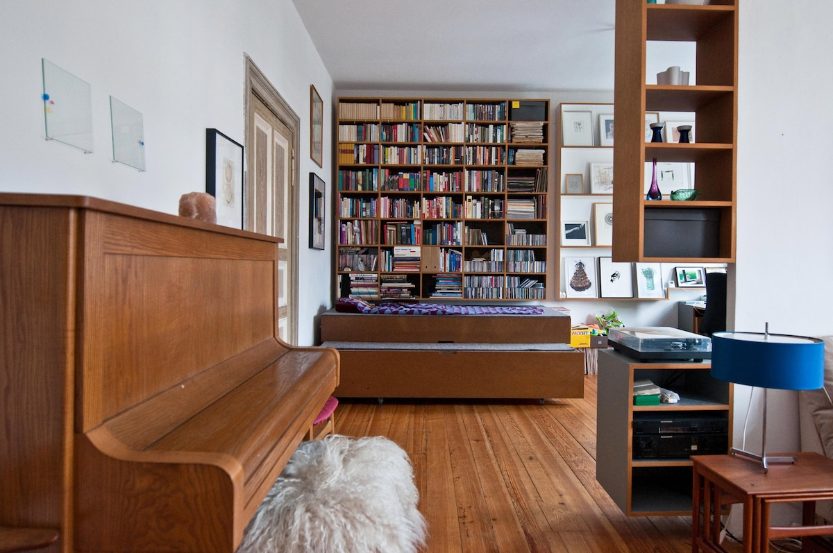 View from the living room into the office space, a guestbed for two people is in the case below the bookshelf