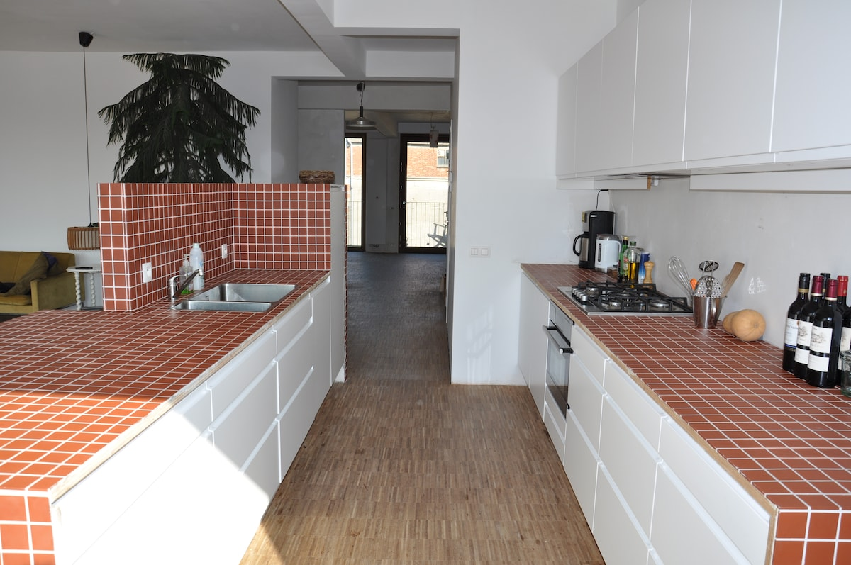The kitchen with in the back, the main door to the balcony
