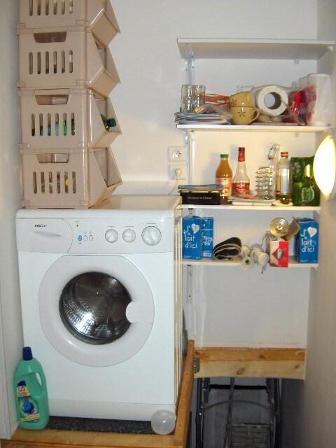 en haut de l escalier un petit cellier avec machine à laver