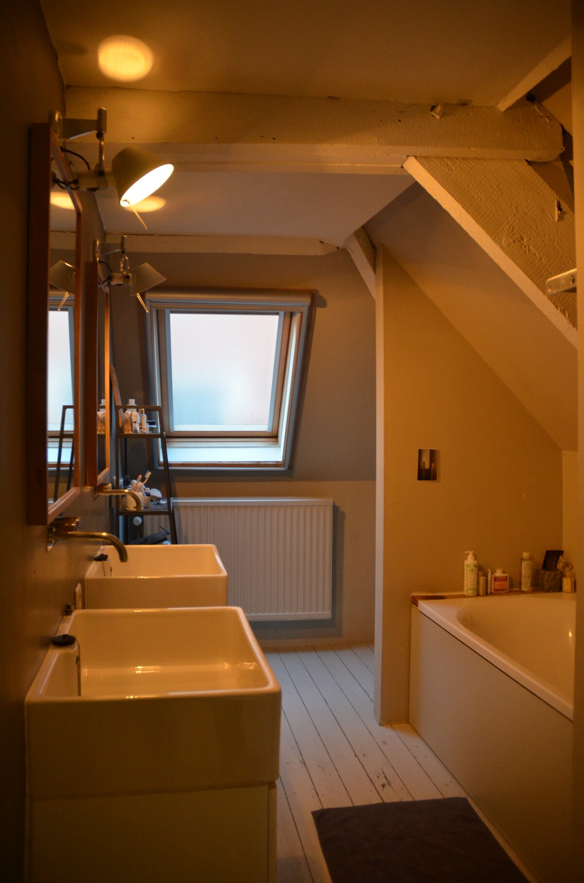 Bathroom with bath tub, shower and two sinks and behind another small/children room