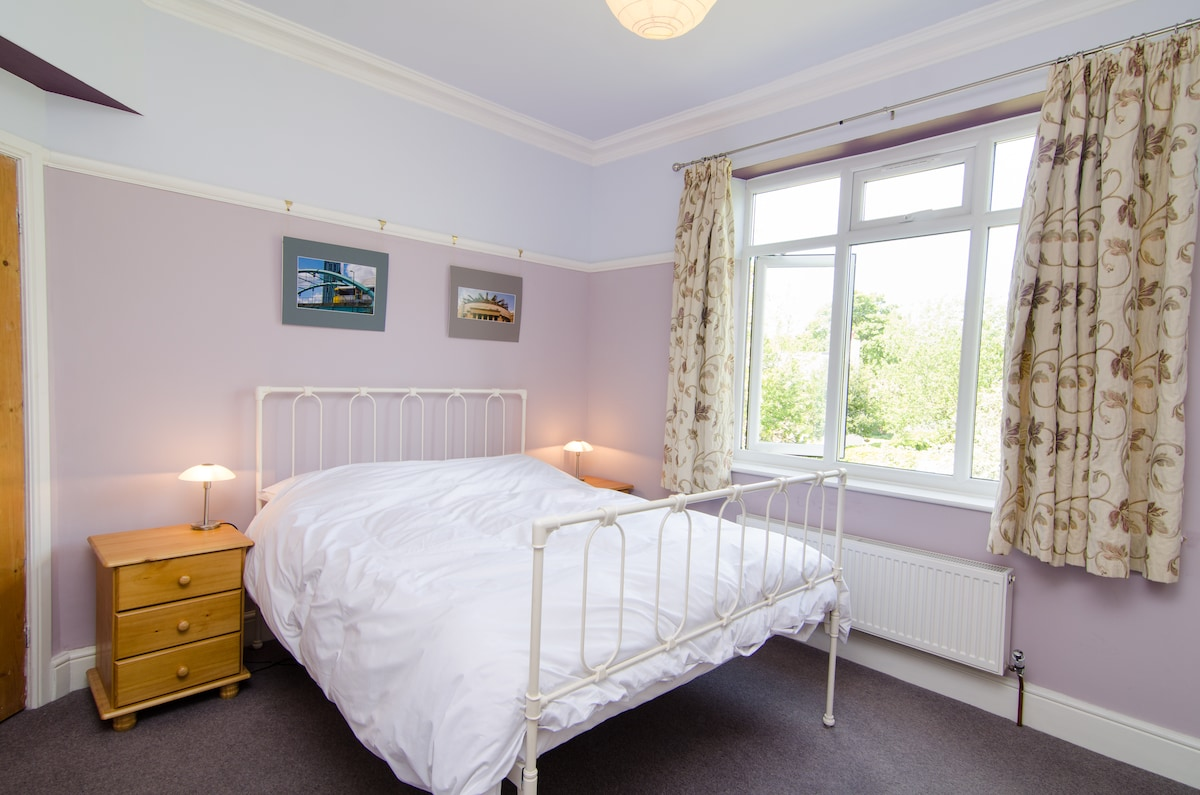 The bedroom has a king-sized bed and a view of the rear garden