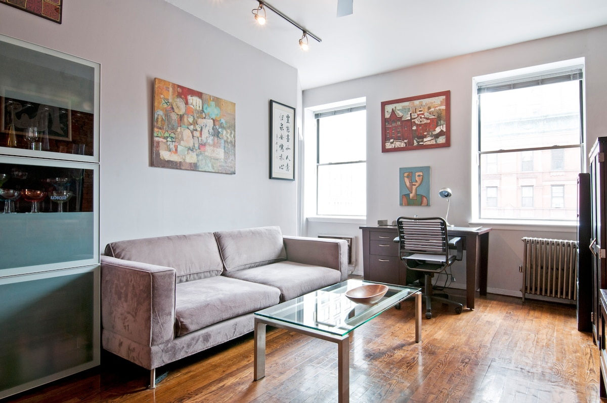 The living room features a large, comfortable couch by Ian Schrager, where you can relax, watch TV, news or Netflix, and enjoy a meal or drink.