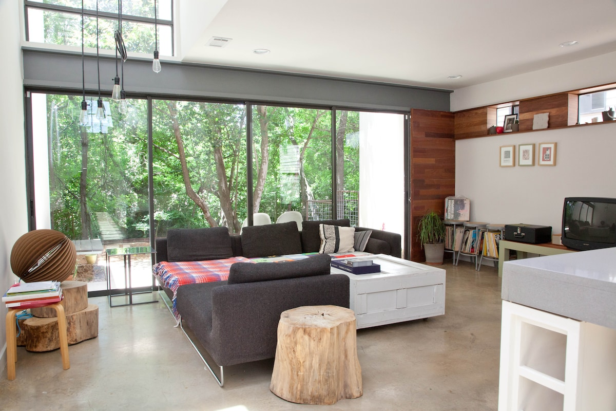 Living room, with giant sliding glass bordering creek behind house.