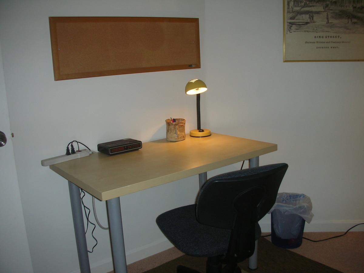 Desk with lamp, radio/alarm clock, and a bulletin board.