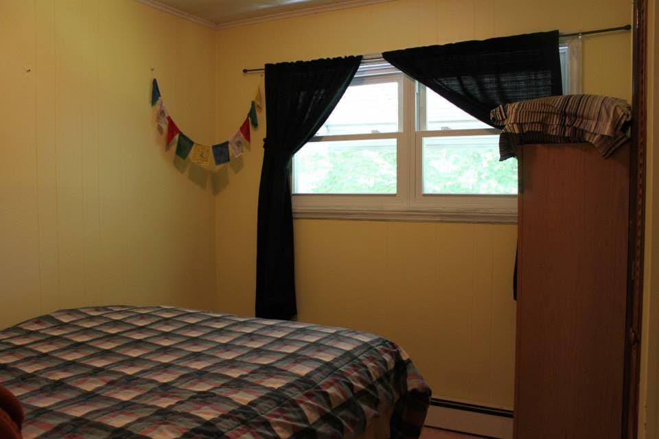 Windows in bedroom overlook back yard, has closet and mini-armoire