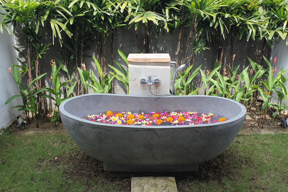 The magnificent polished stone bath tub. Soak up the night air under the stairs and  melt away all your worries!