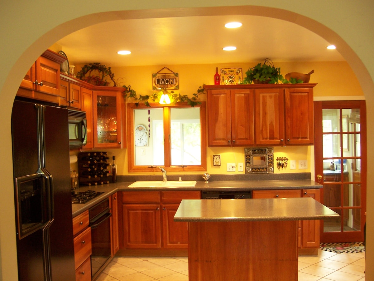 Warm welcoming kitchen, with four bar stools for gathering in the kitchen.