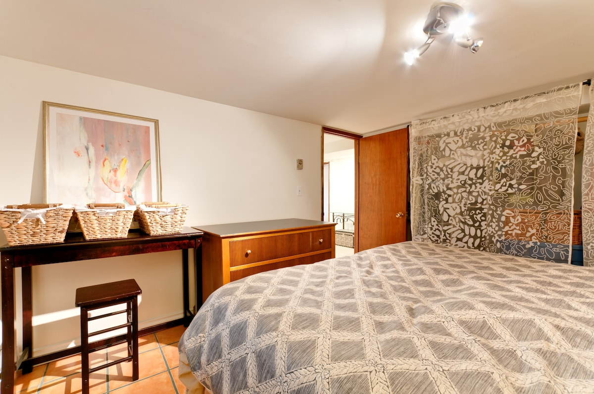 The bedroom, queen size bed. There is also a working desk in front.