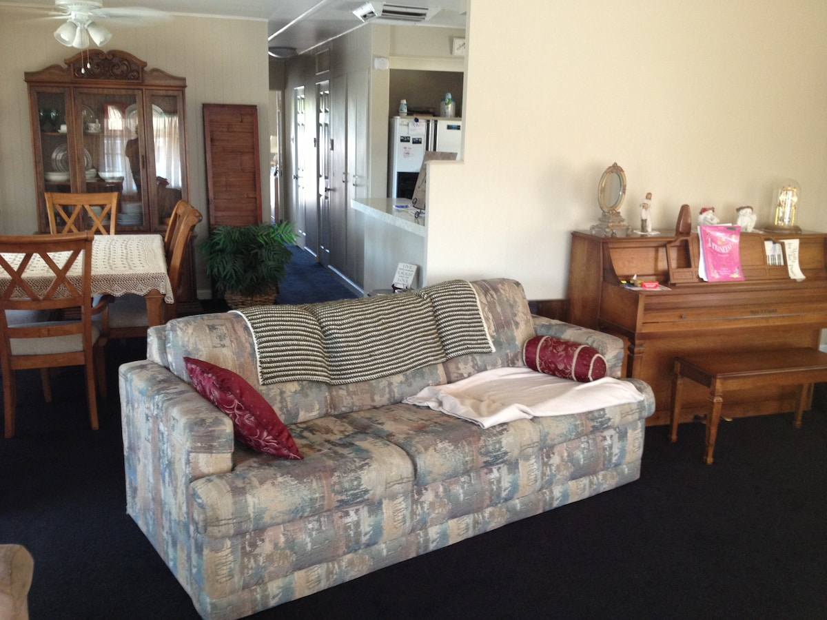 Living room with couch that opens to queen bed, dining room & kitchen