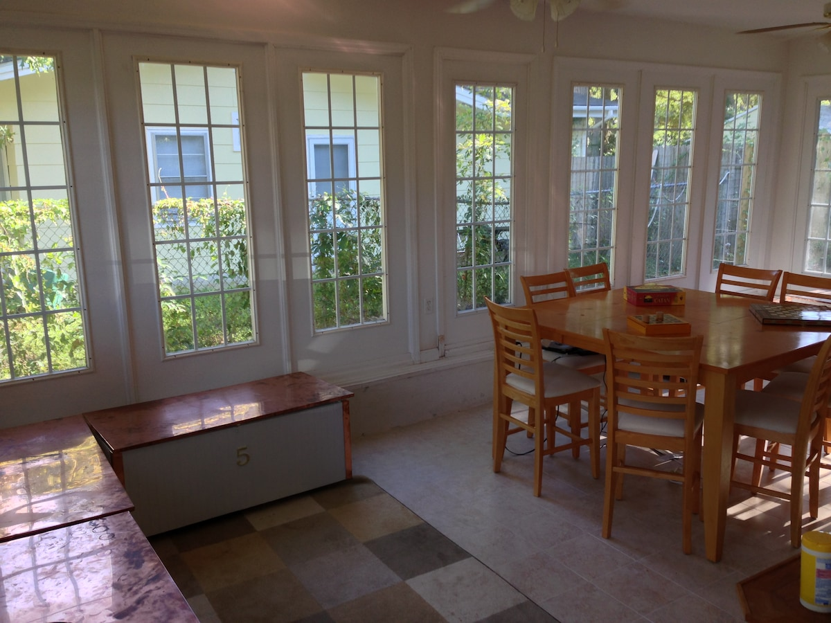 Glass sun/game room with large gaming table, multiple copper topped trunks, games, ceiling fans and tile floors.