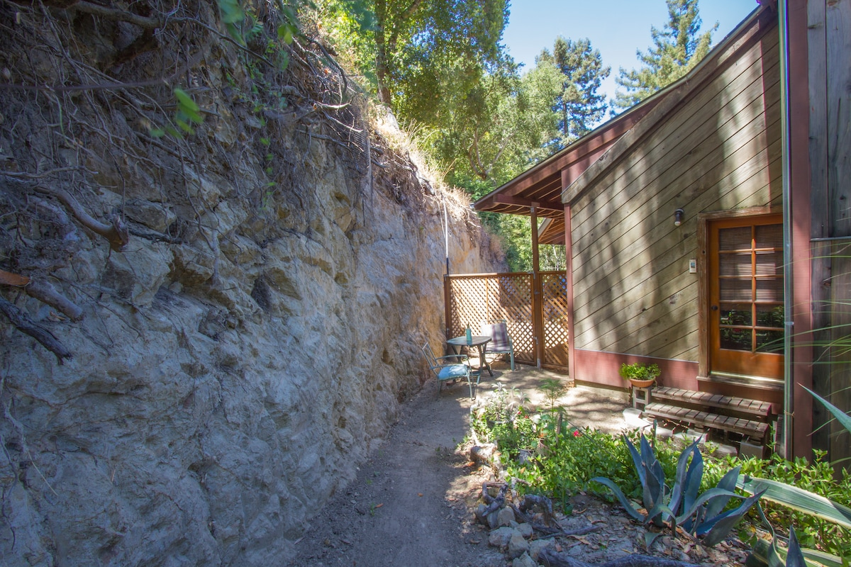 Entrance features rock wall carved from the mountain with access to garden and camping.