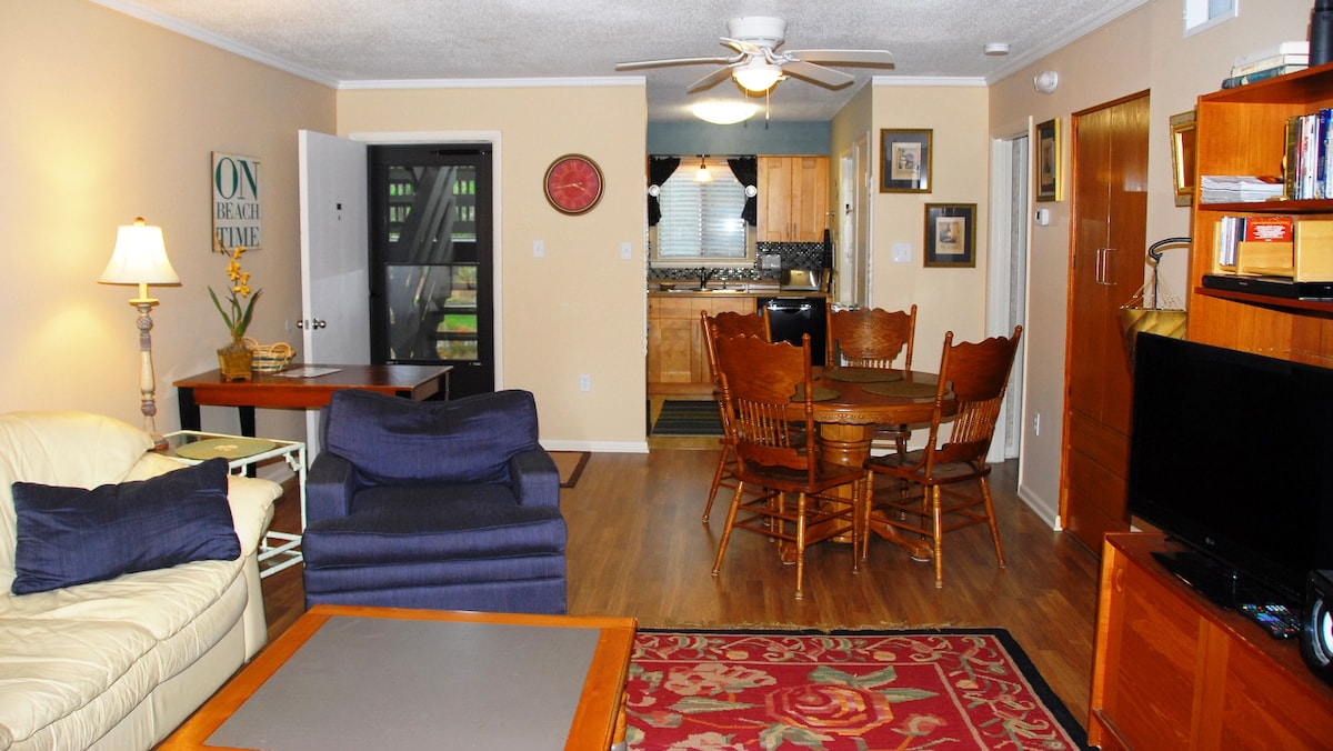 Living room, dining area and kitchen viewed from the balcony doorway.