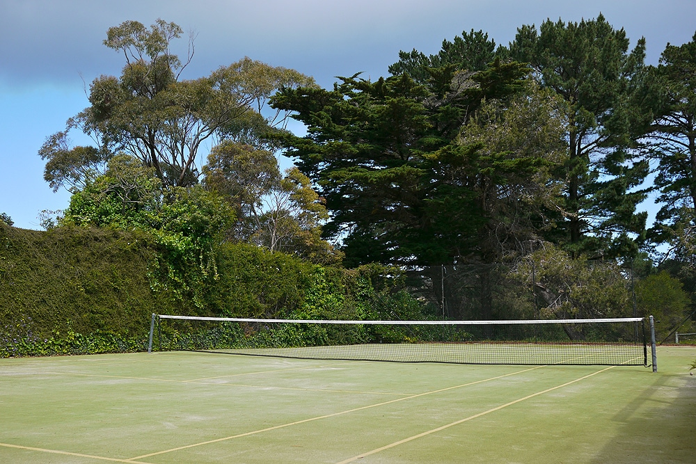 Completely private full size tennis court, surrounded by established trees and overlooking Sorrento Golf Course