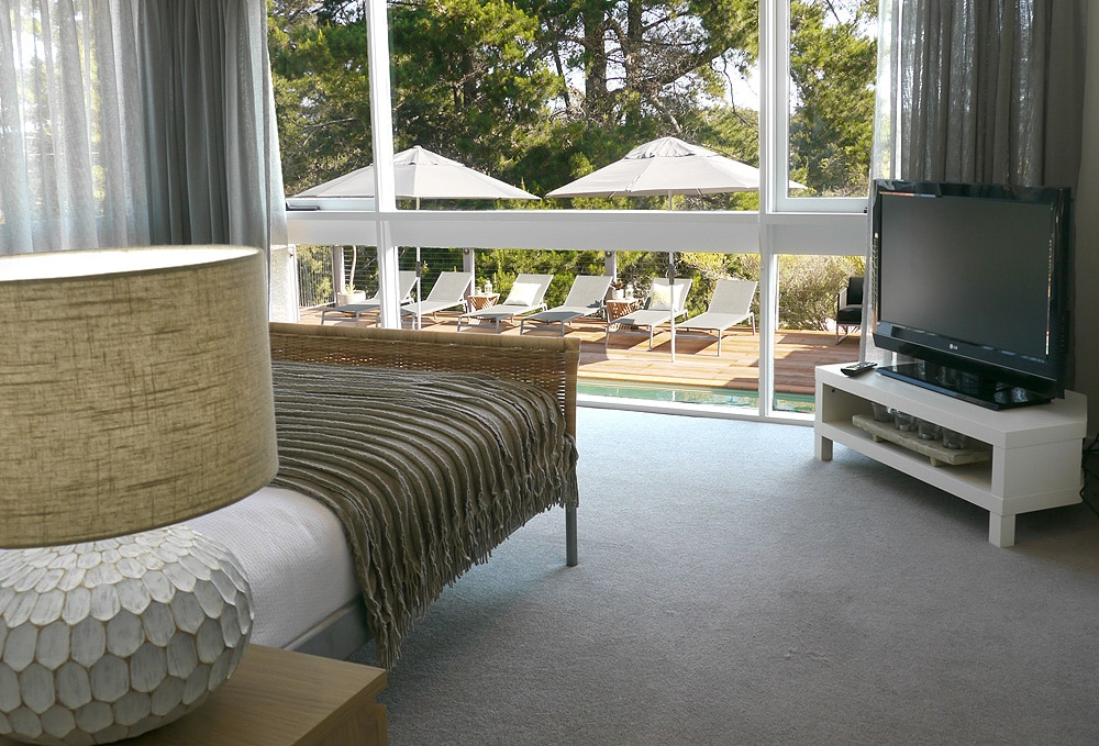 Master bedroom with flat screen TV, ensuite, and overlooking pool and golf course