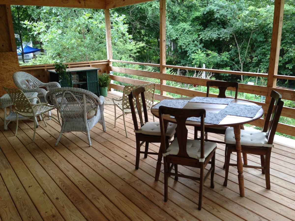 Open porch off the kitchen with views of the backyard veggie and flower garden.