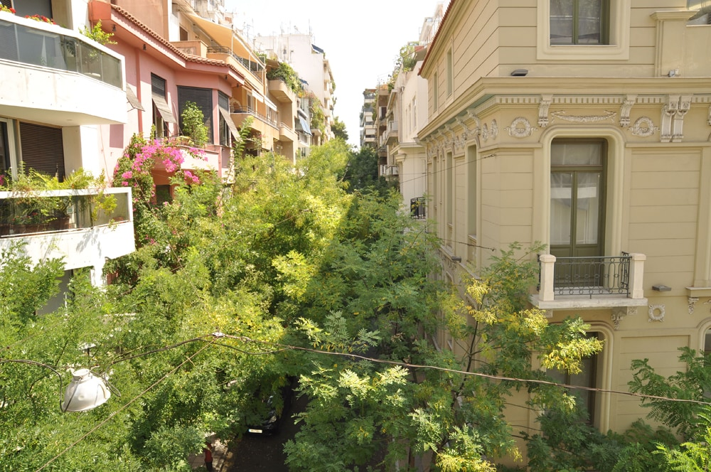 View over a tree-lined street and a classic Athenian building.  As soon as you step out, you find yourself in the most elegant neighbourhood of central Athens frequented by politicians, business people, elegant youth. You feel like a local yourself!