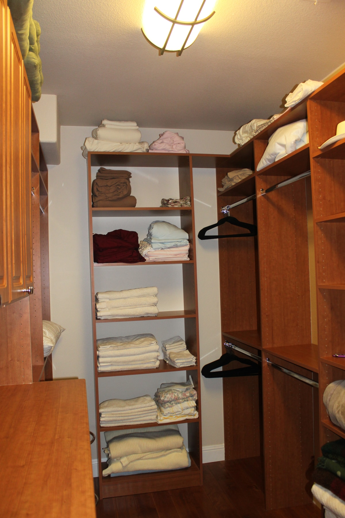 Partial view of large custom walk-in closet with lots of storage a drawer space.