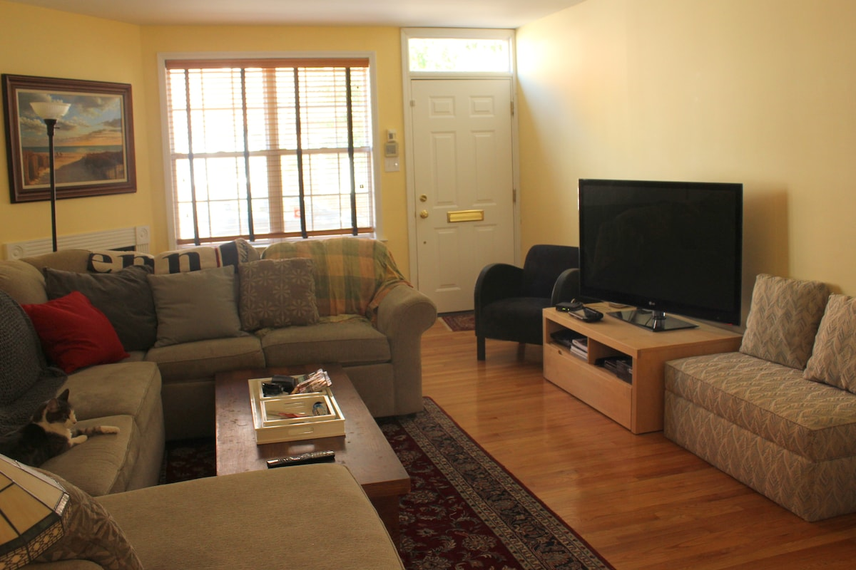 Spacious living room with large, comfortable couch, wood-burning fireplace, and flat screen TV!