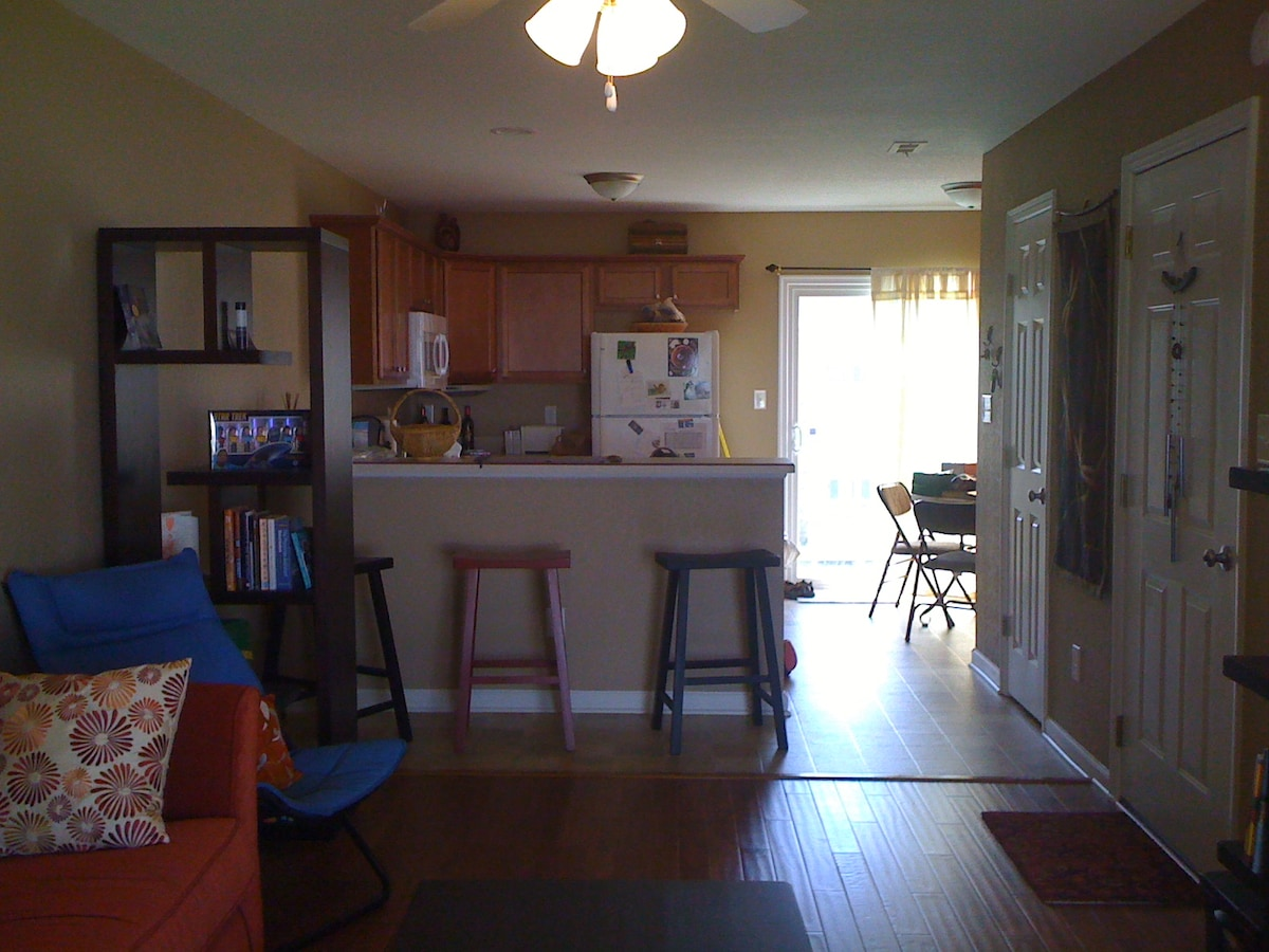 sunny full kitchen with bar and table seating. Flat top range, and dishwasher