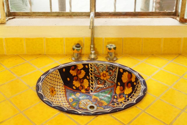 Colorful glazed kitchen sink on tiled countertops.