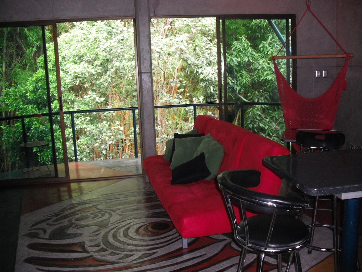 Area social con exuberante vista 100% natural con balcón al rio y jardín.