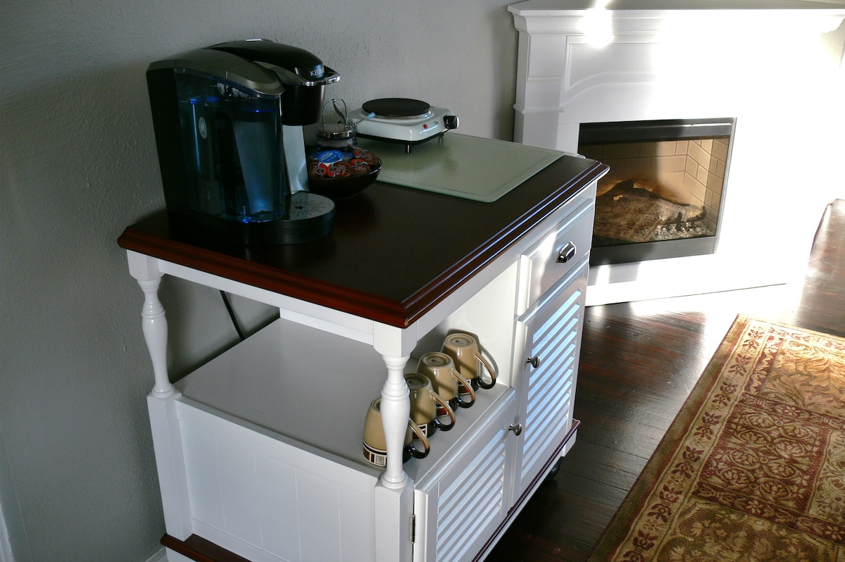 Our new electric heater fireplace, kitchen station with added burner, coffee maker, and pots and pans in the cabinets below