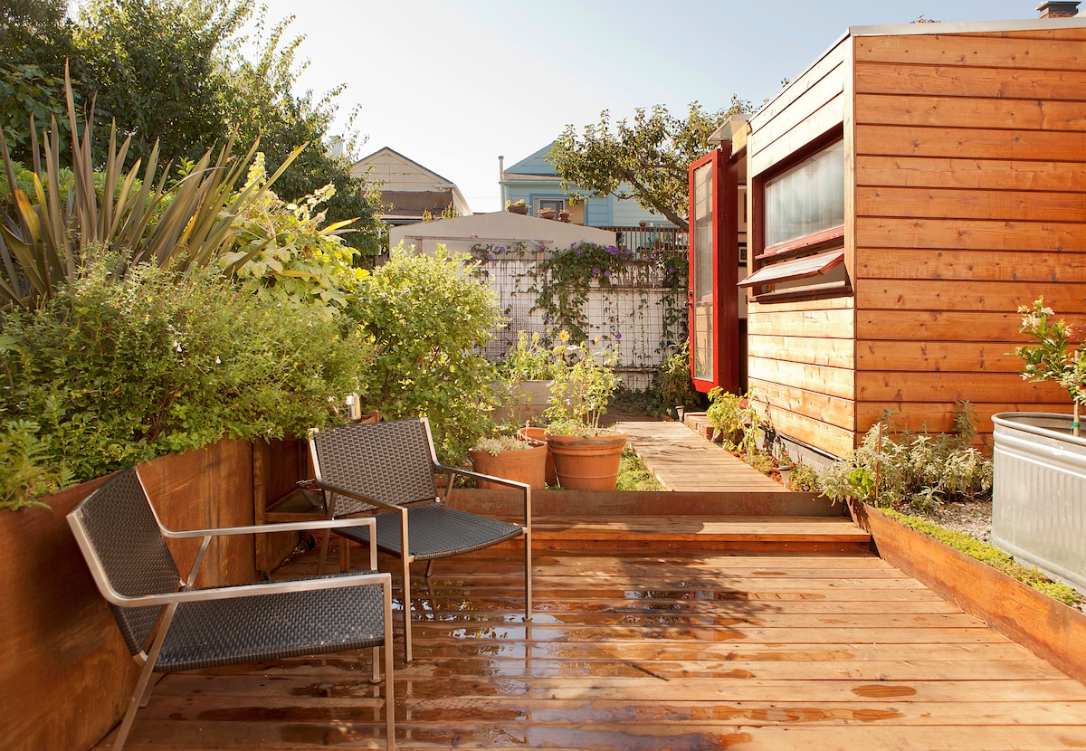 The sunny redwood deck, garden and steps to the cabana.